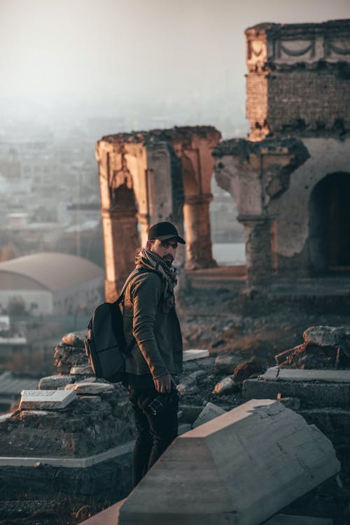 Man Wearing Cap and Backpack Standing on Ruins