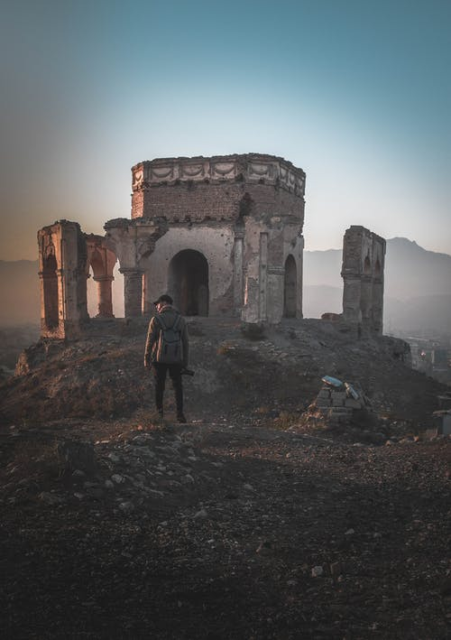Man Standing on Ruins Digital Wallpaper