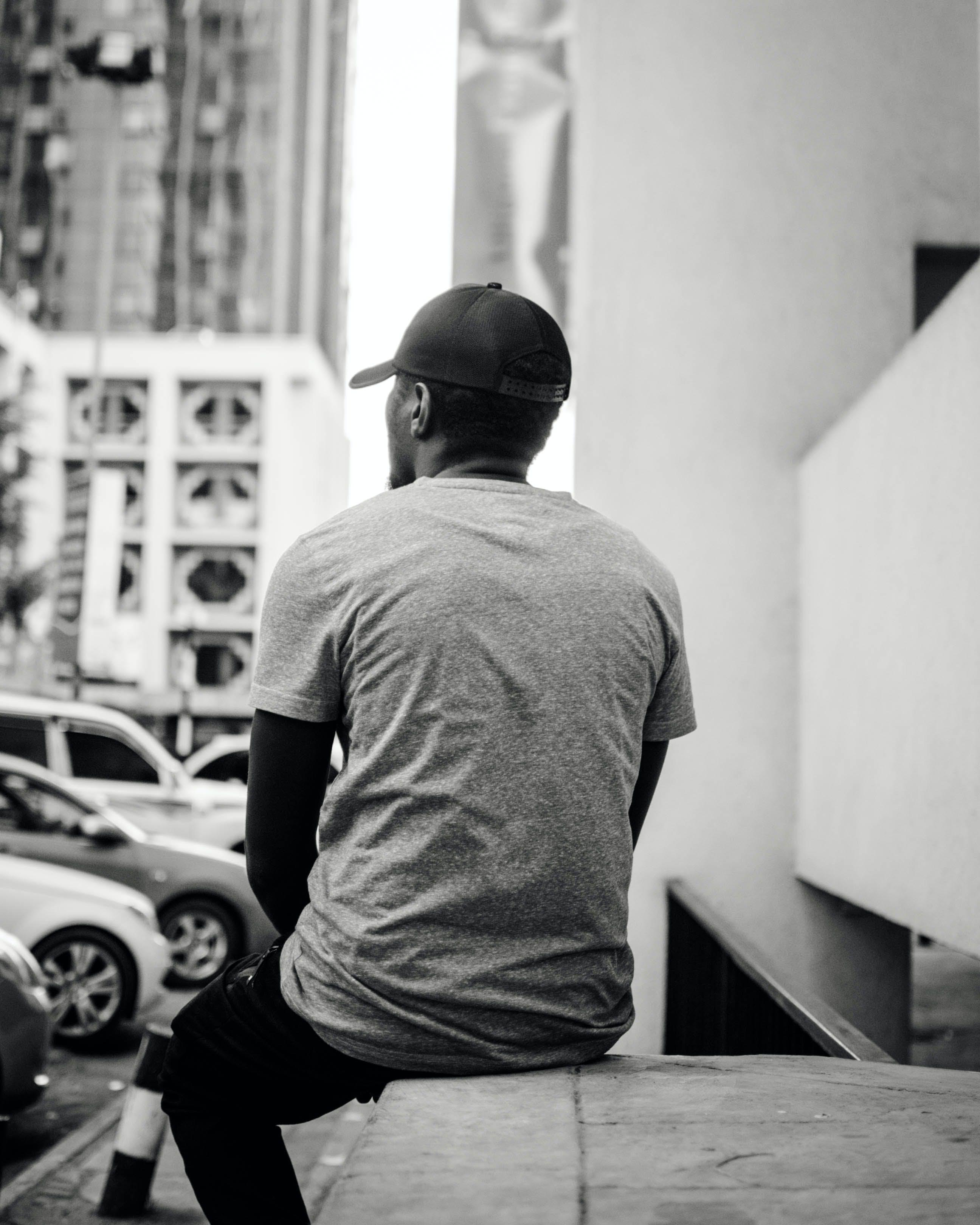 Monochrome Photo of Man Sitting On Ledge