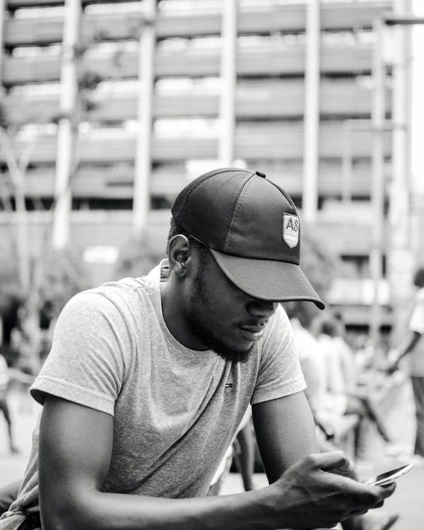 Monochrome Photo of Man Texting