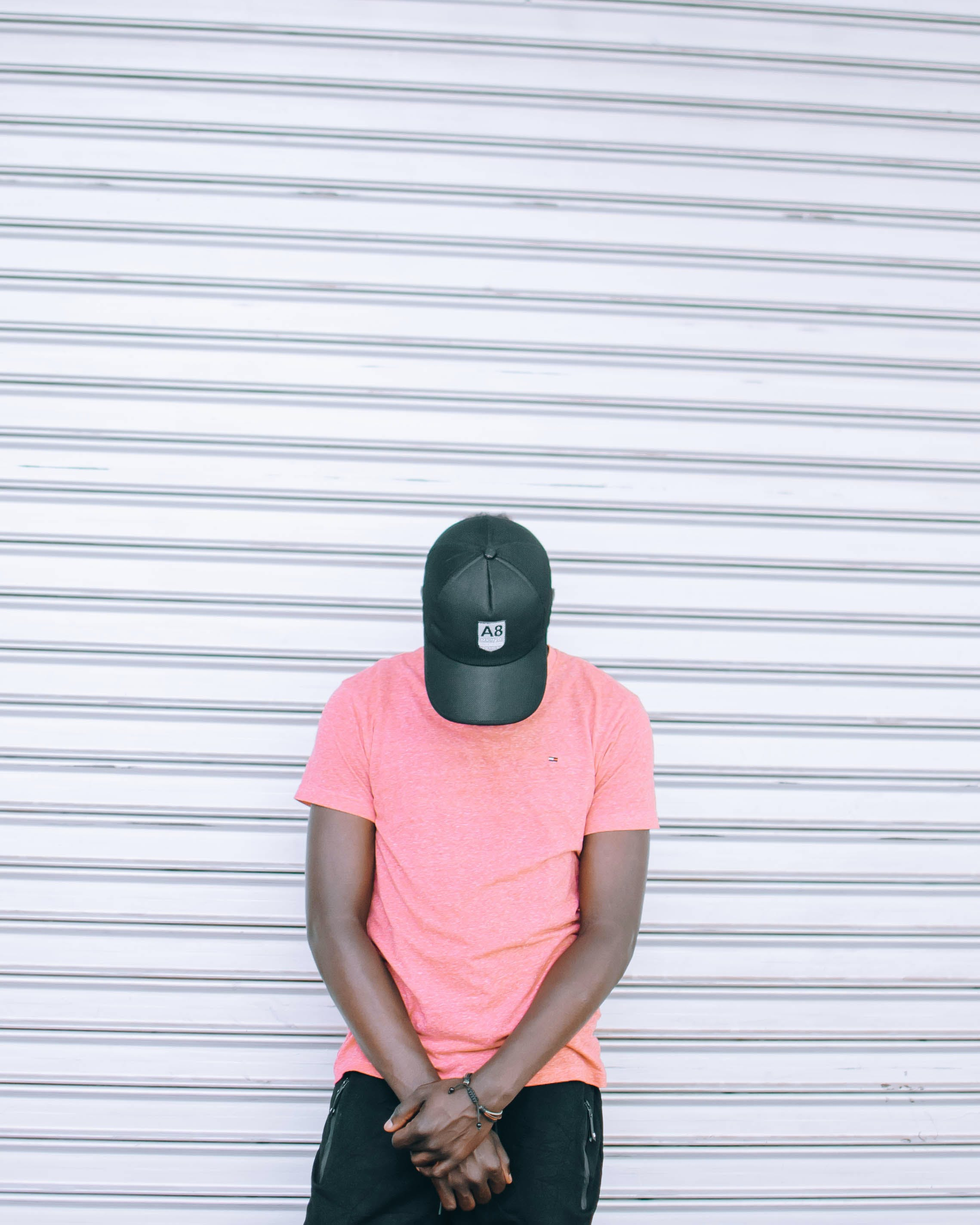 Man Wearing Pink Tee Shirt Leaning on Wall While Head Down