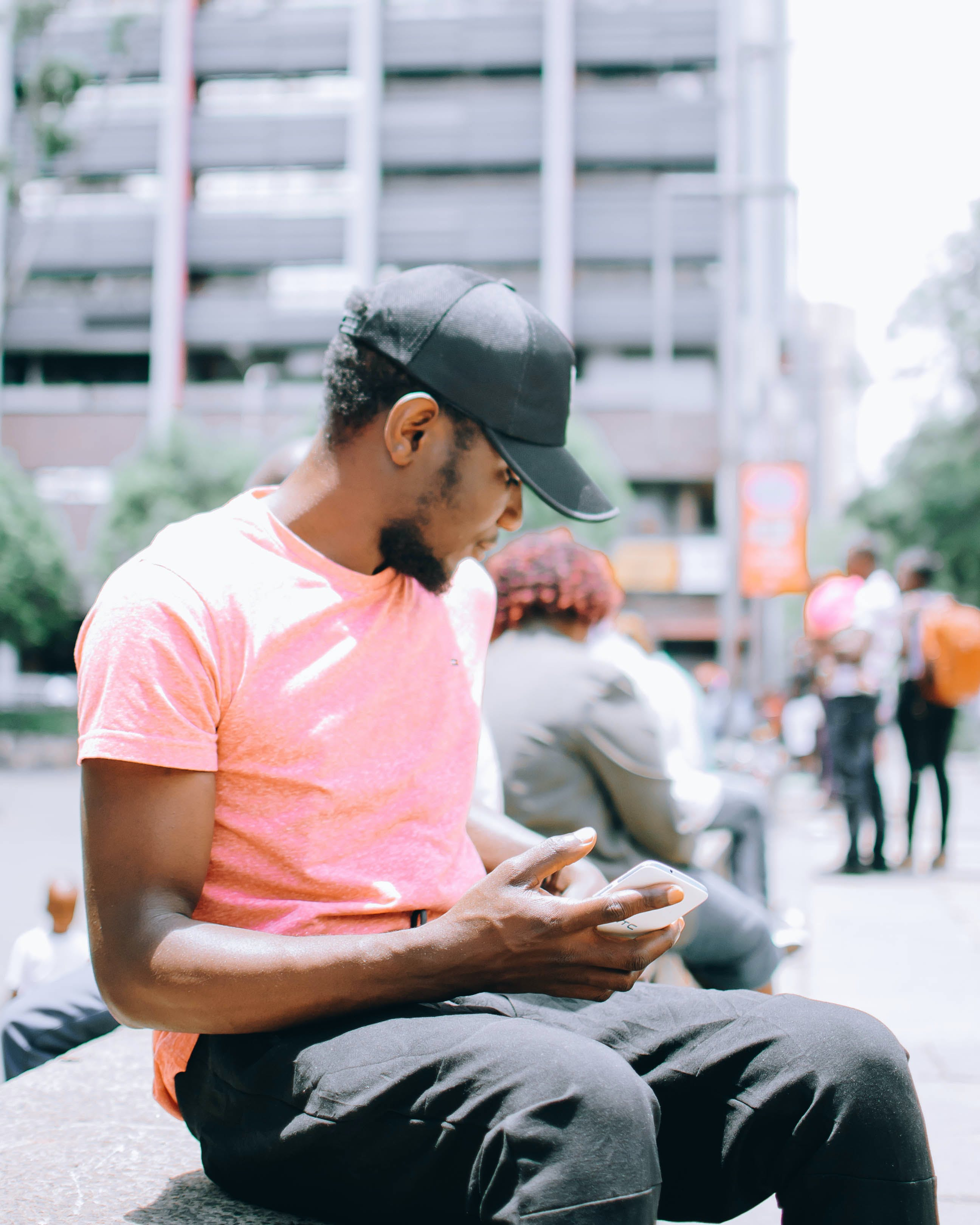 Man Sitting on Gray Bench While Using Mobile Phone