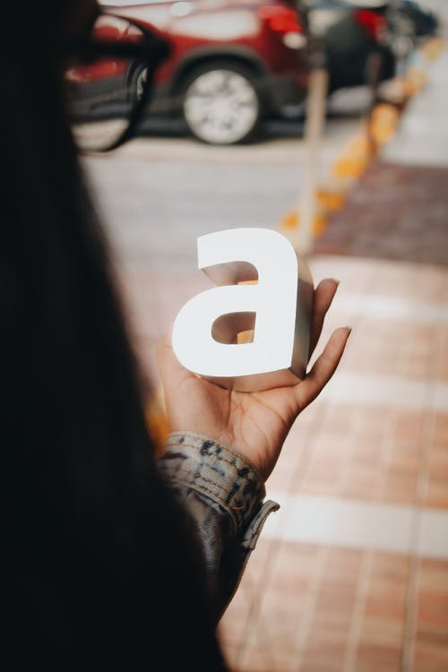 Tilt-shift Lens Photography of Person Holding A-letter