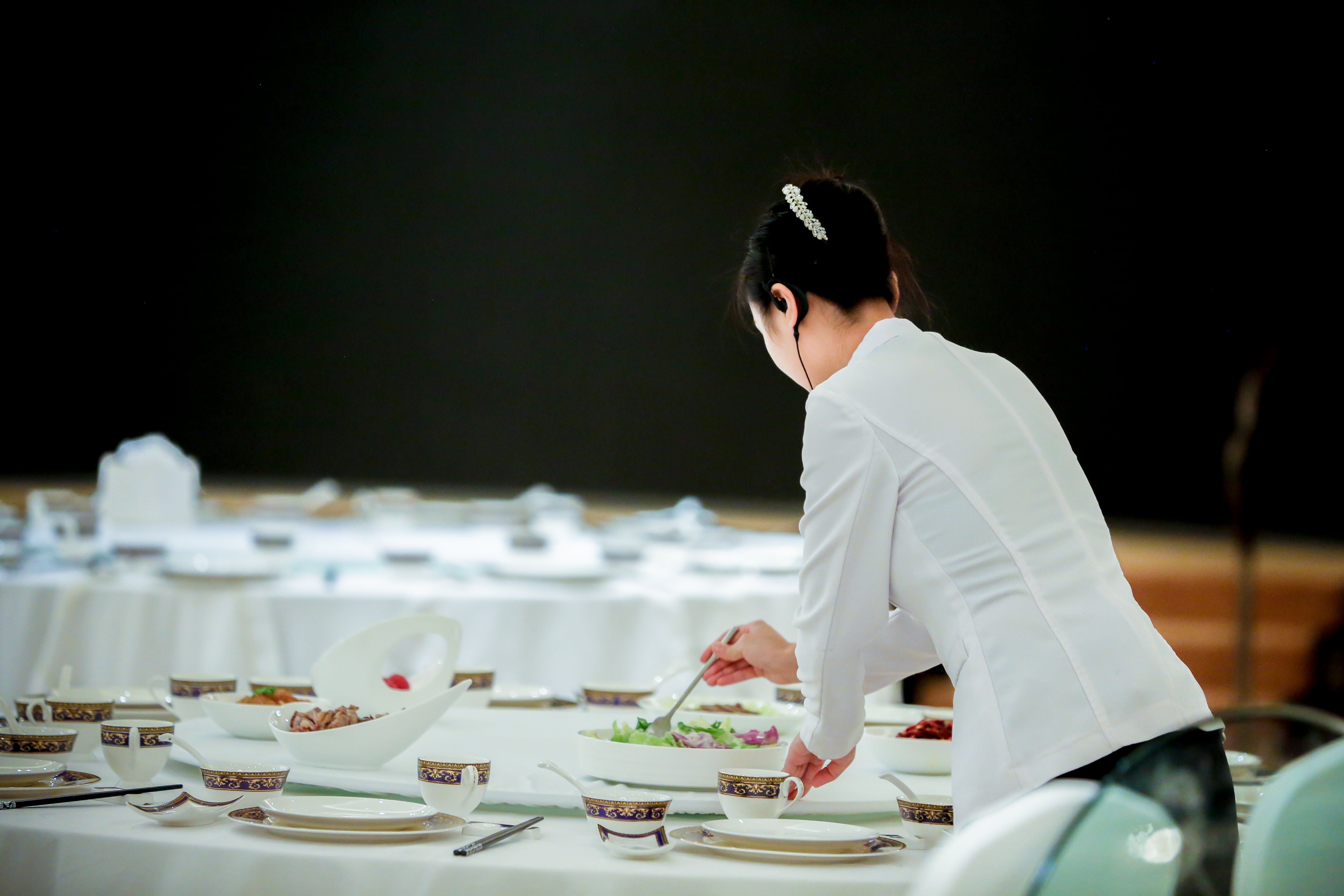 Woman Preparing Dish on Table