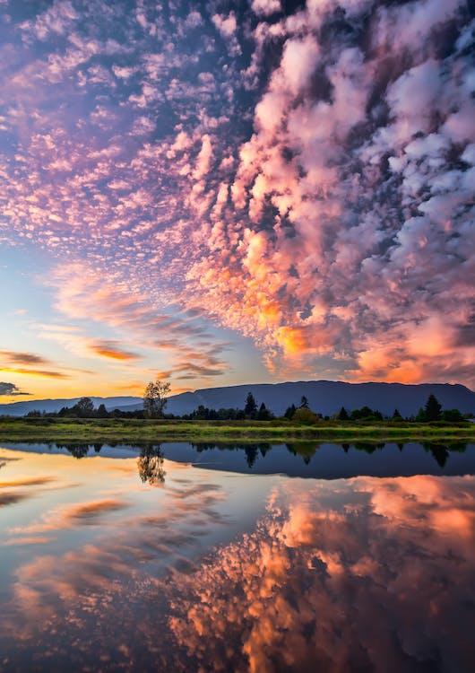 青い空に覆われた雲の対称写真