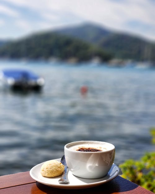 Close-up Photo of White Ceramic Teacup on Saucer Beside Body of Water