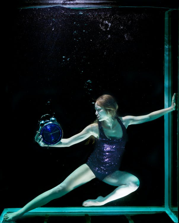 Woman In Underwater Holding Round Blue Analog Bell Alarm Clock