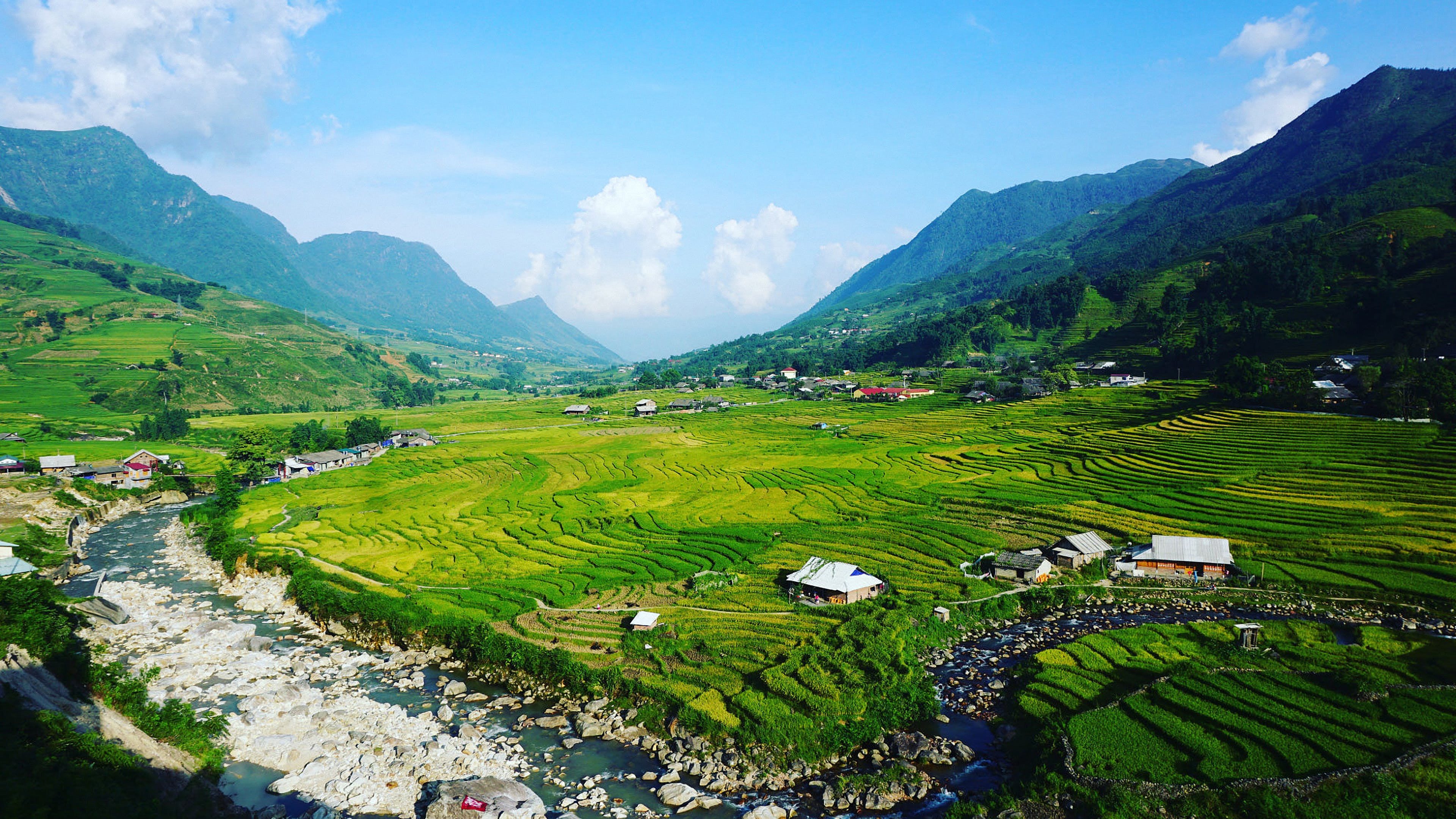 Green Fields Surrounded by Mountains Under Blue Cloudy Sky