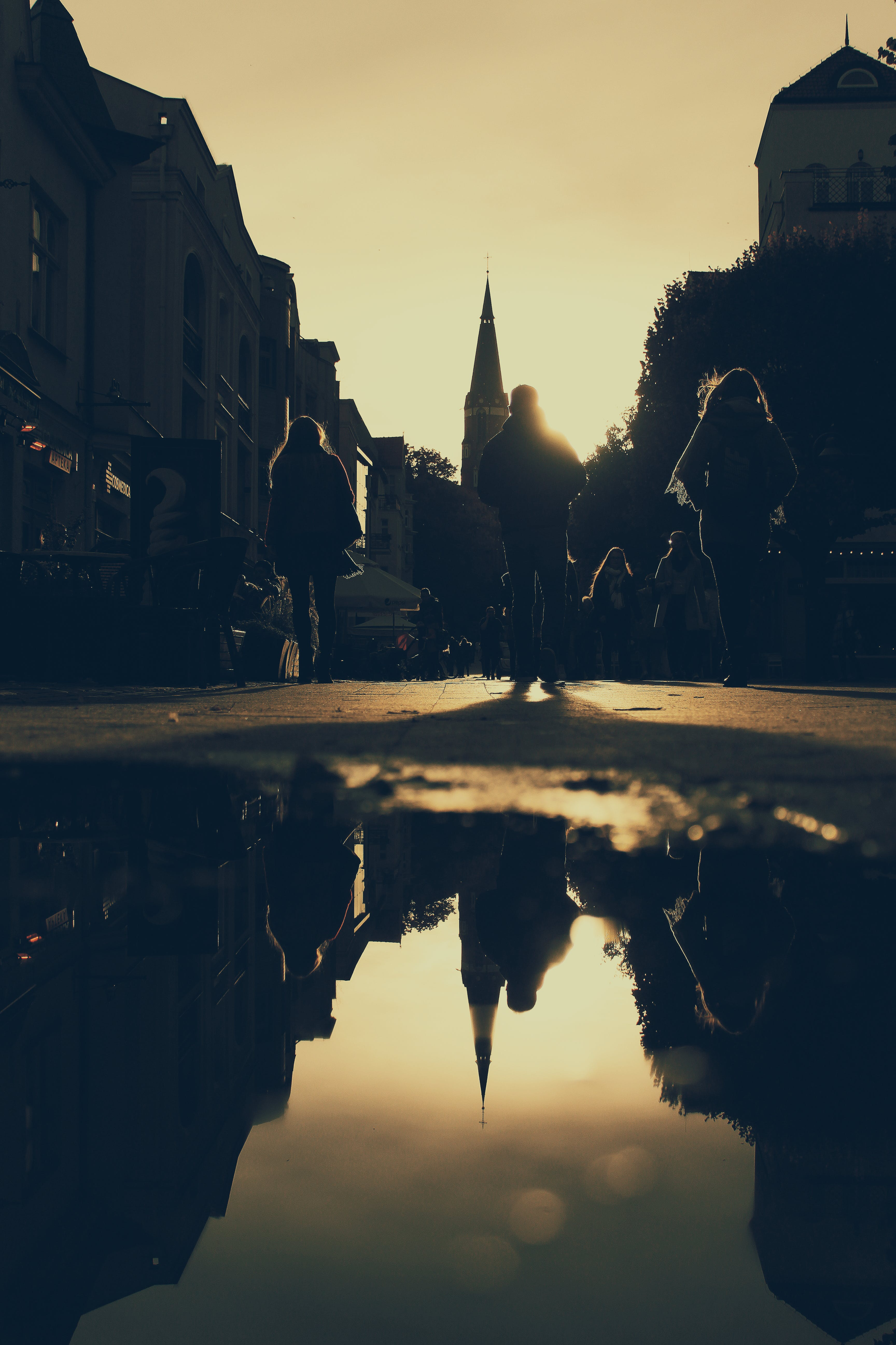 Silhouette of People Walking on Street Reflected on Puddle