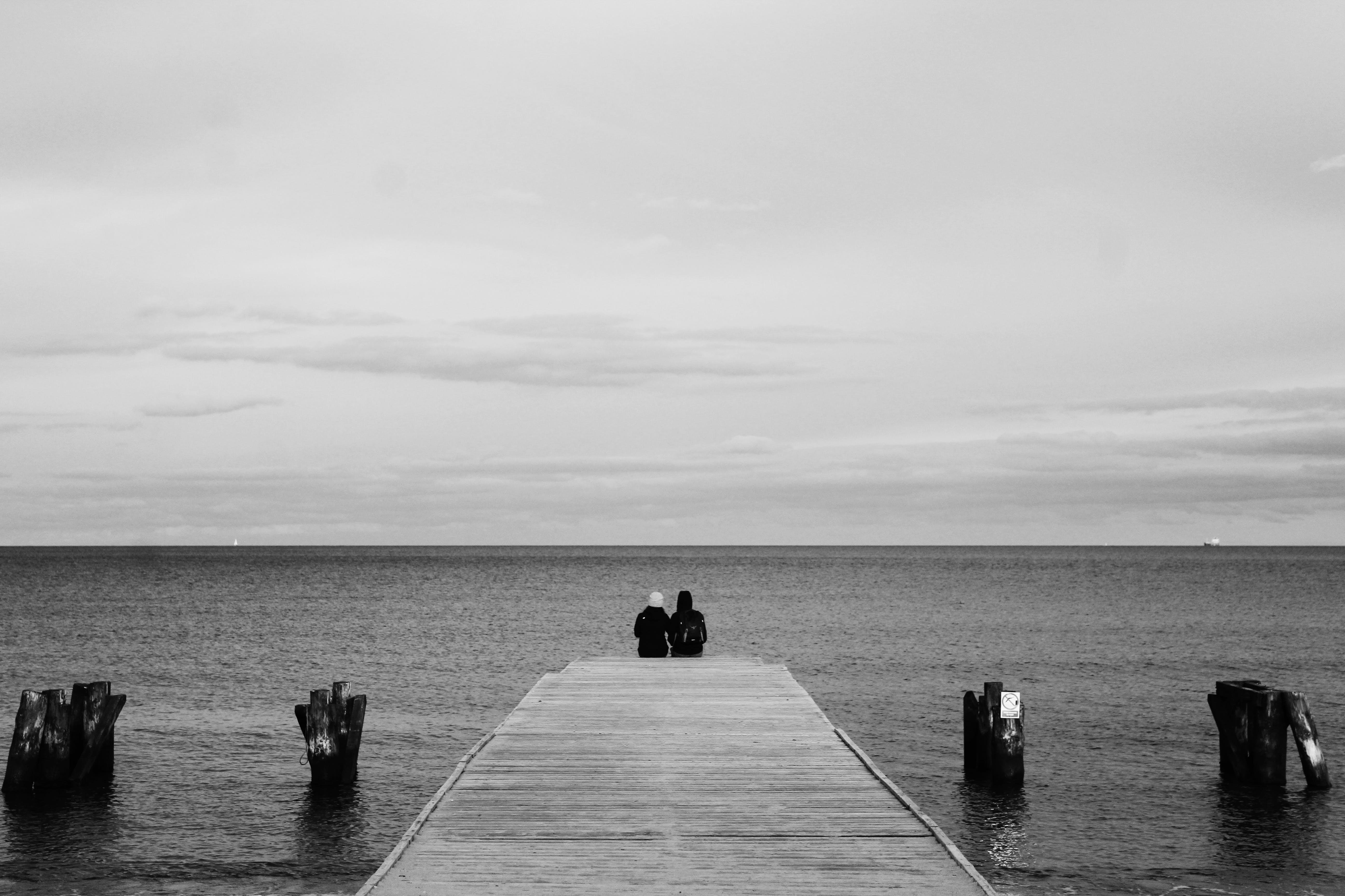 Grayscale Photography of Couple Sitting on Wood Dock