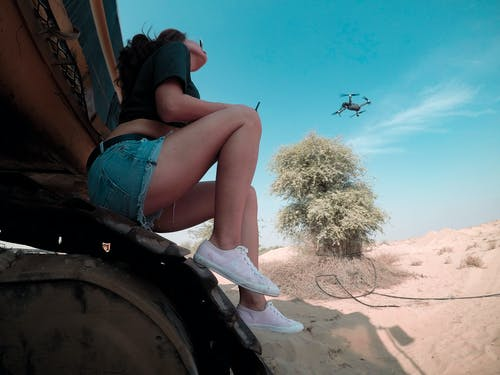 Woman Wears Blue Denim Short Shorts and Black Quadcopter Drone Under Clear Blue Sky