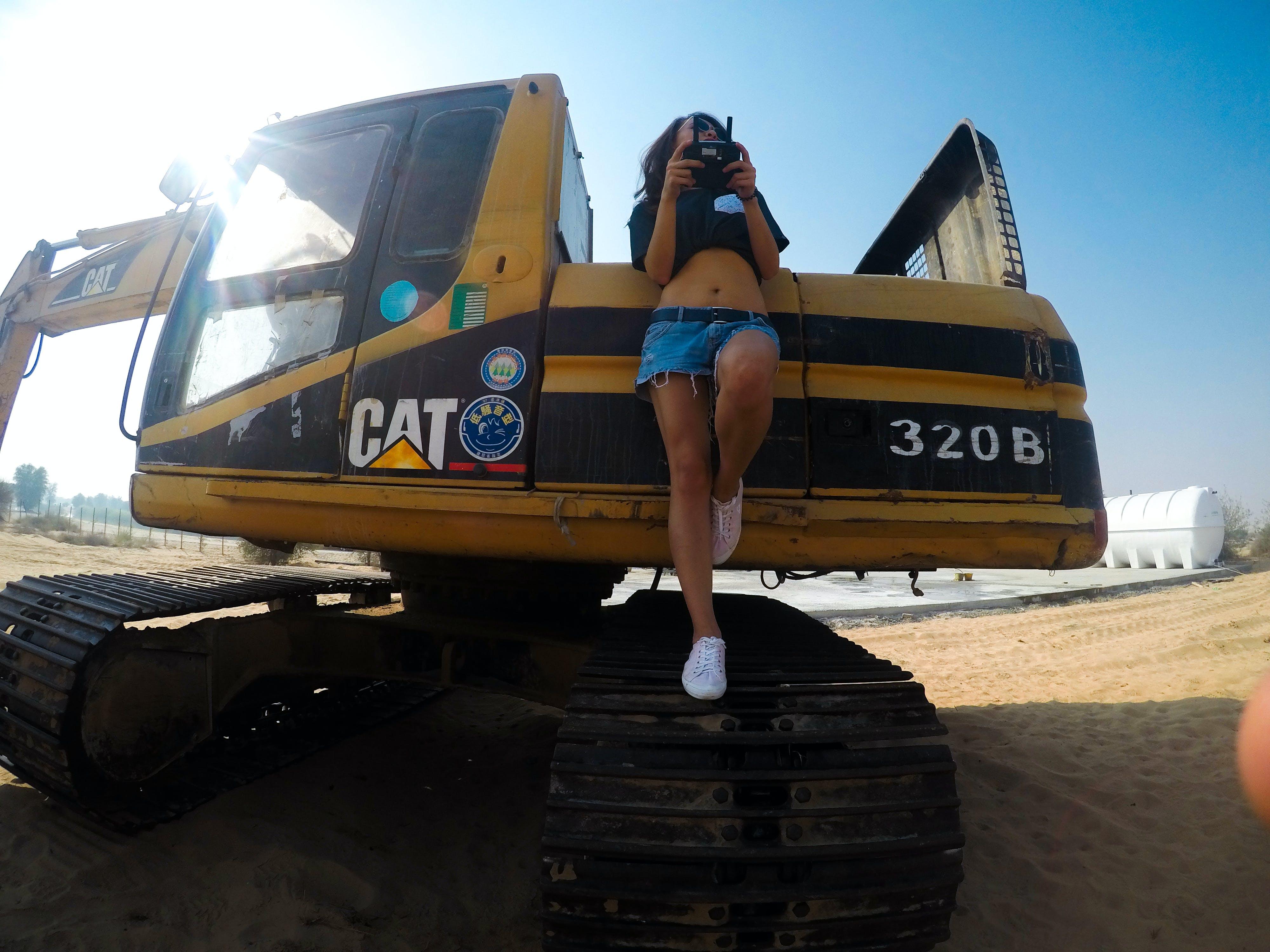 Woman Standing on Cat 320b Excavator