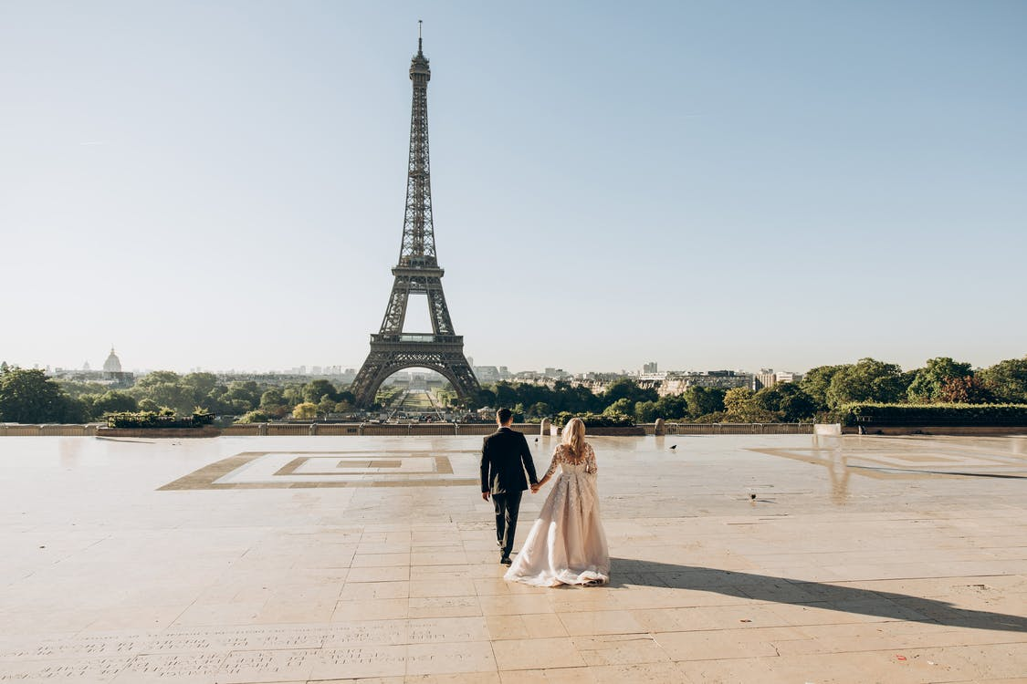 Woman and Man Walking in Park in Front of Eiffel Tower