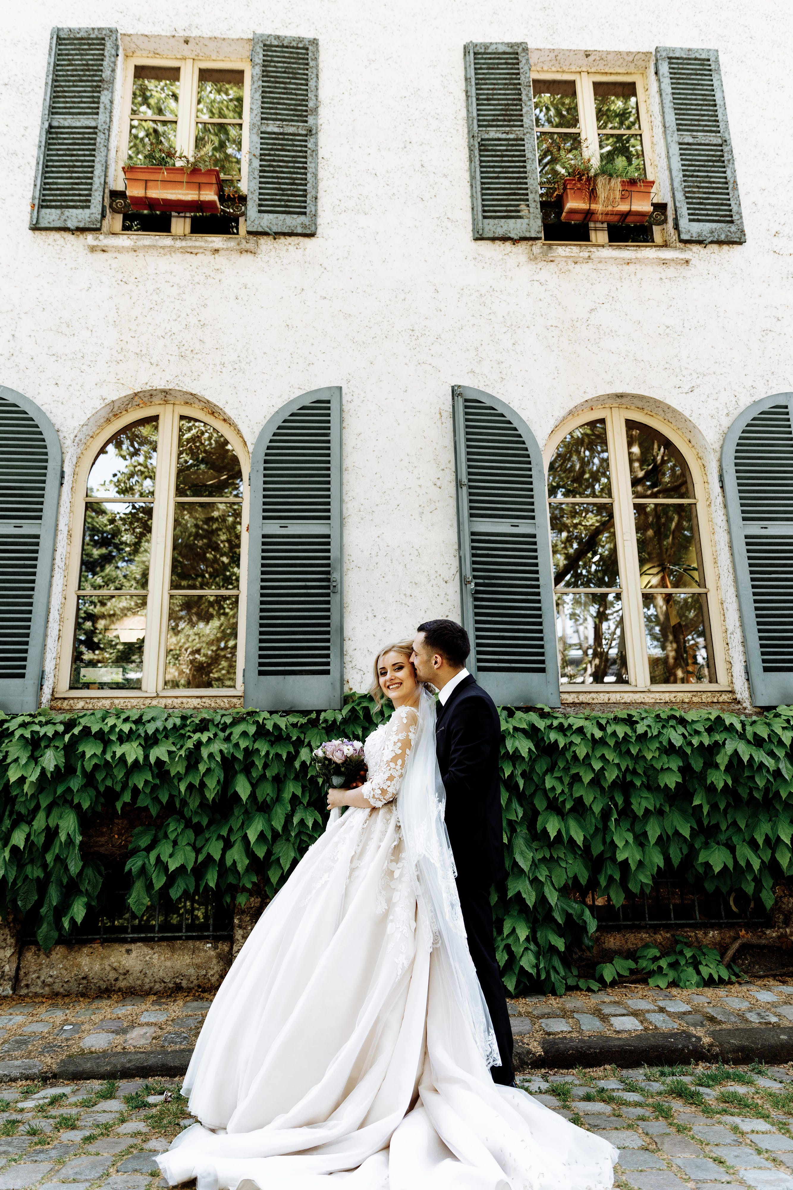 Photo of Bride and Groom Standing Near House