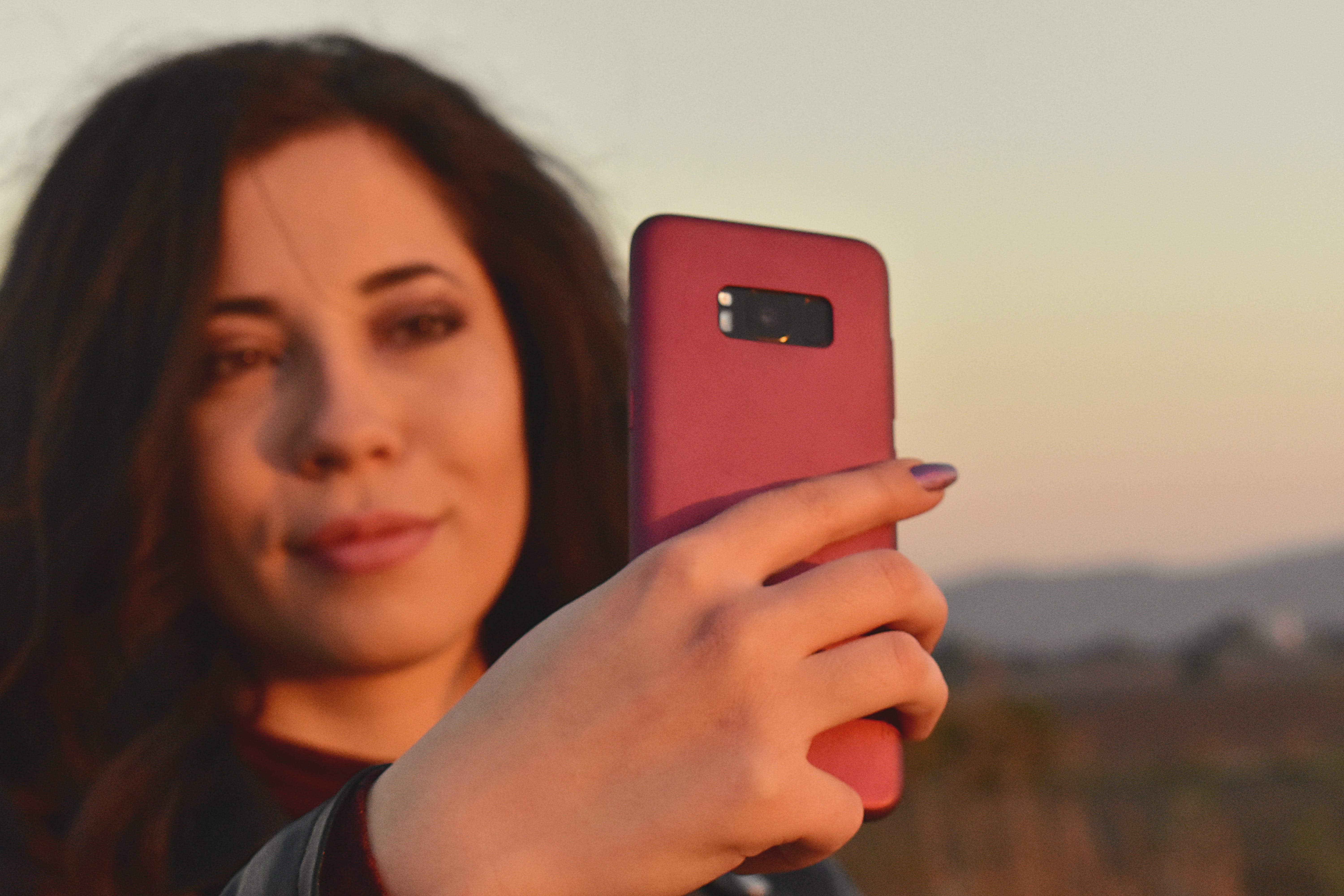 Woman Holding Midnight Black Samsung Galaxy S8+ With Red Case