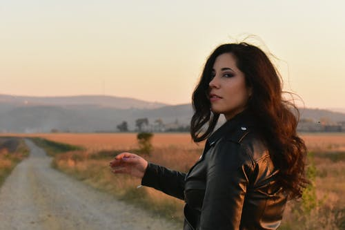Woman Wearing Black Leather Jacket Standing on Gray Pathway