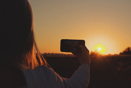 Silhouette Photo of Woman Taking Photo of Sunset