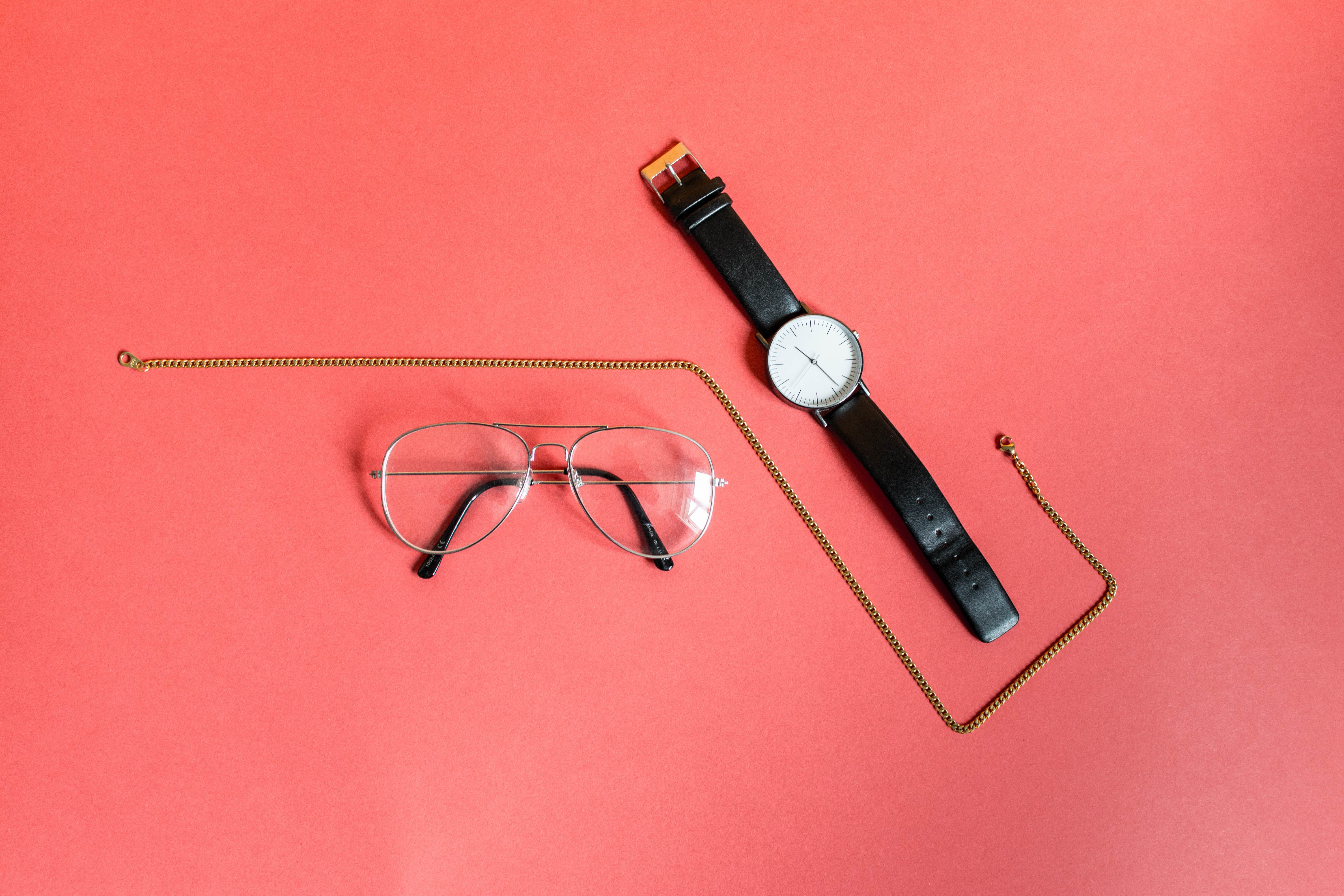Gold-colored Necklace in Between Analog Watch and Eyeglasses on Pink Surface