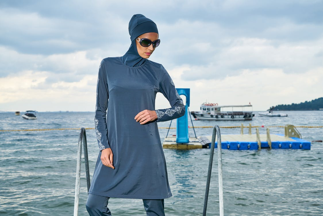 Woman in Blue Hijab and Long-sleeved Dress Standing Near Body of Water