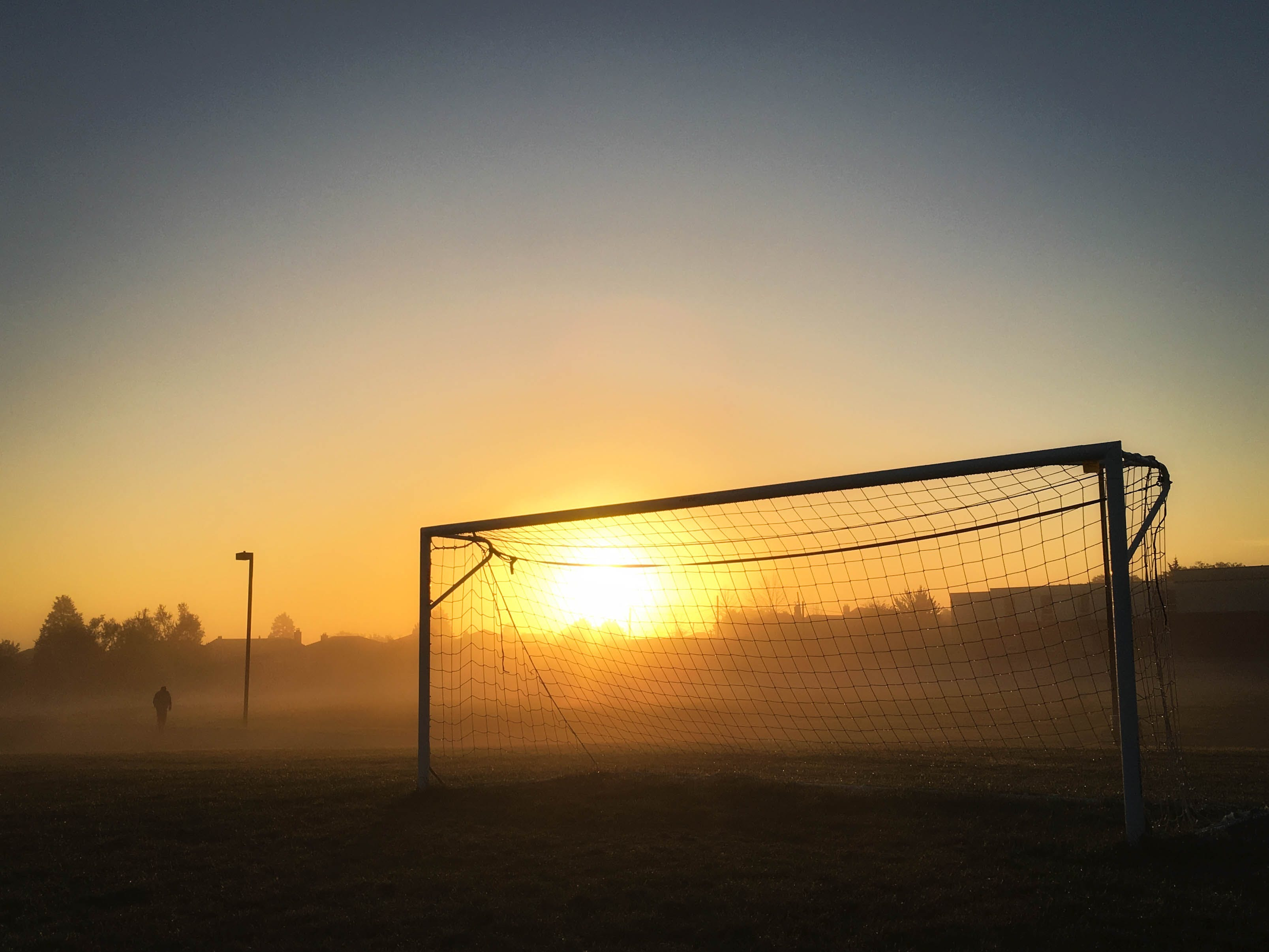 Person Jogging Near Soccer Goal during Sunrise