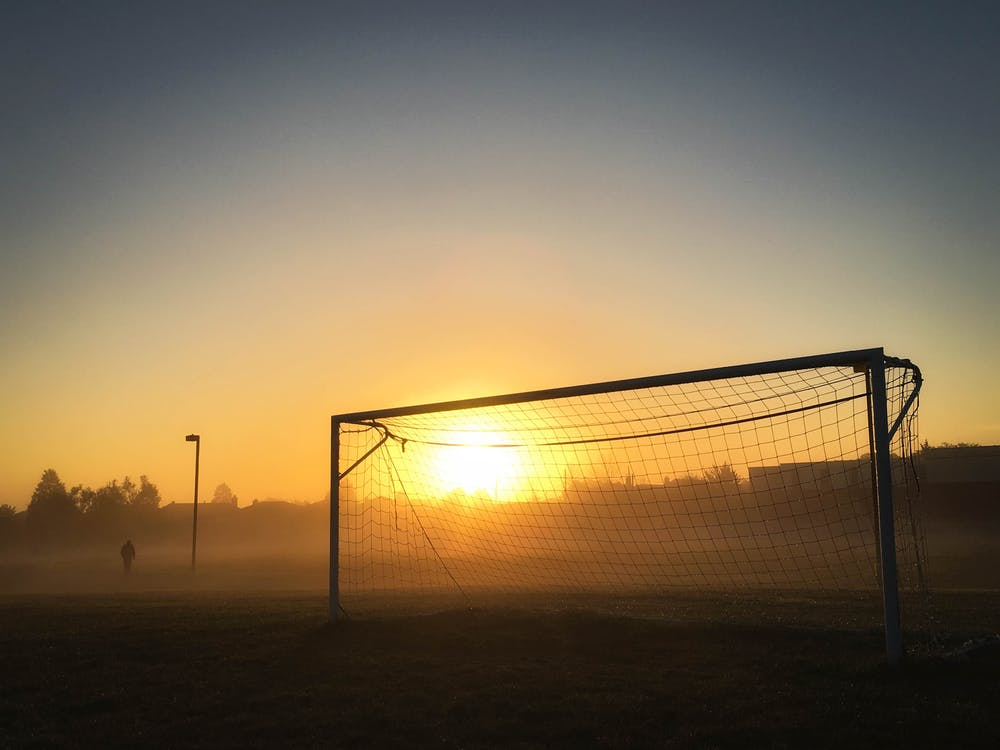 Person Jogging Near Soccer Goal during Sunrise