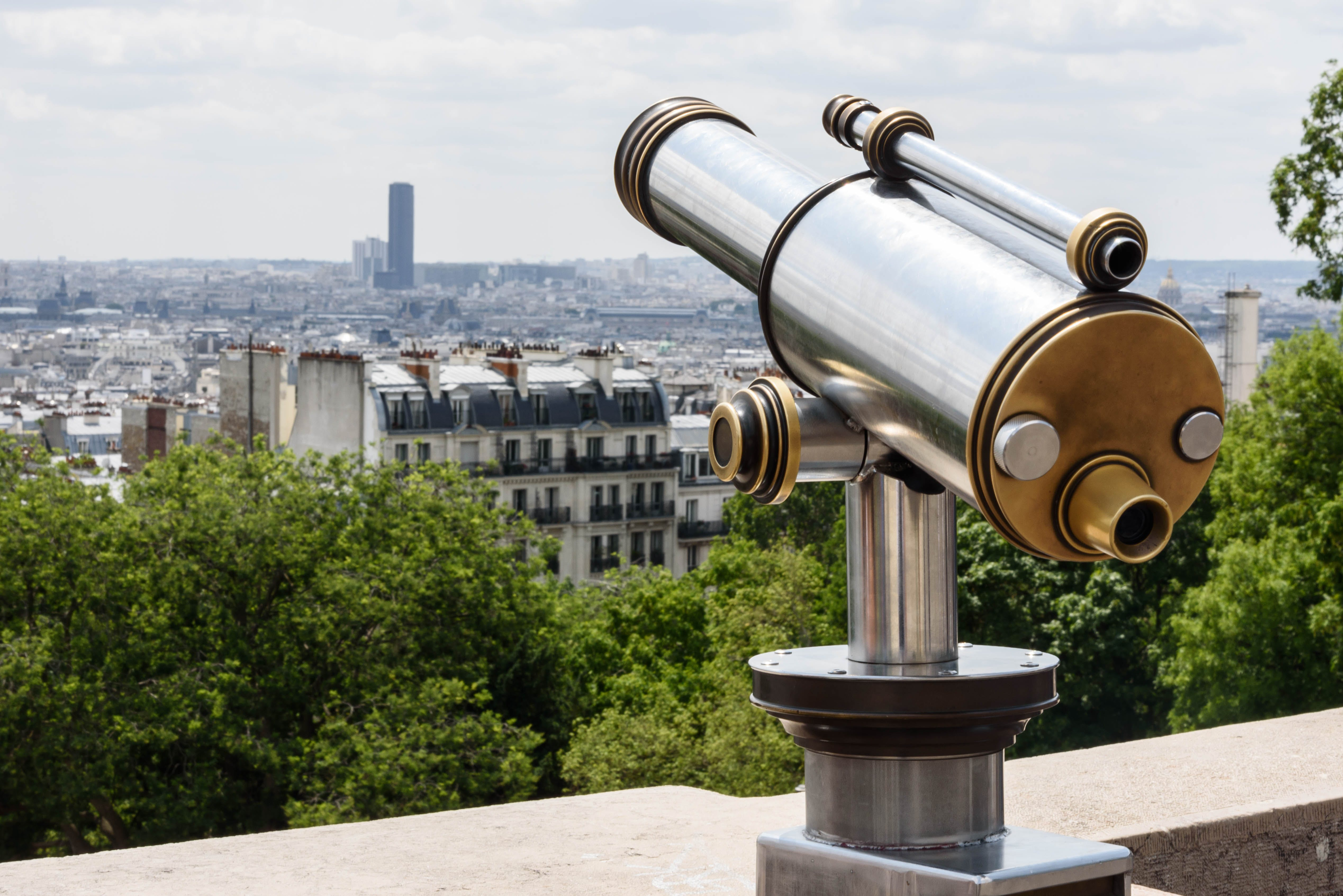 Gray and Brown Tower Telescope Near Trees and High Rise Buildings