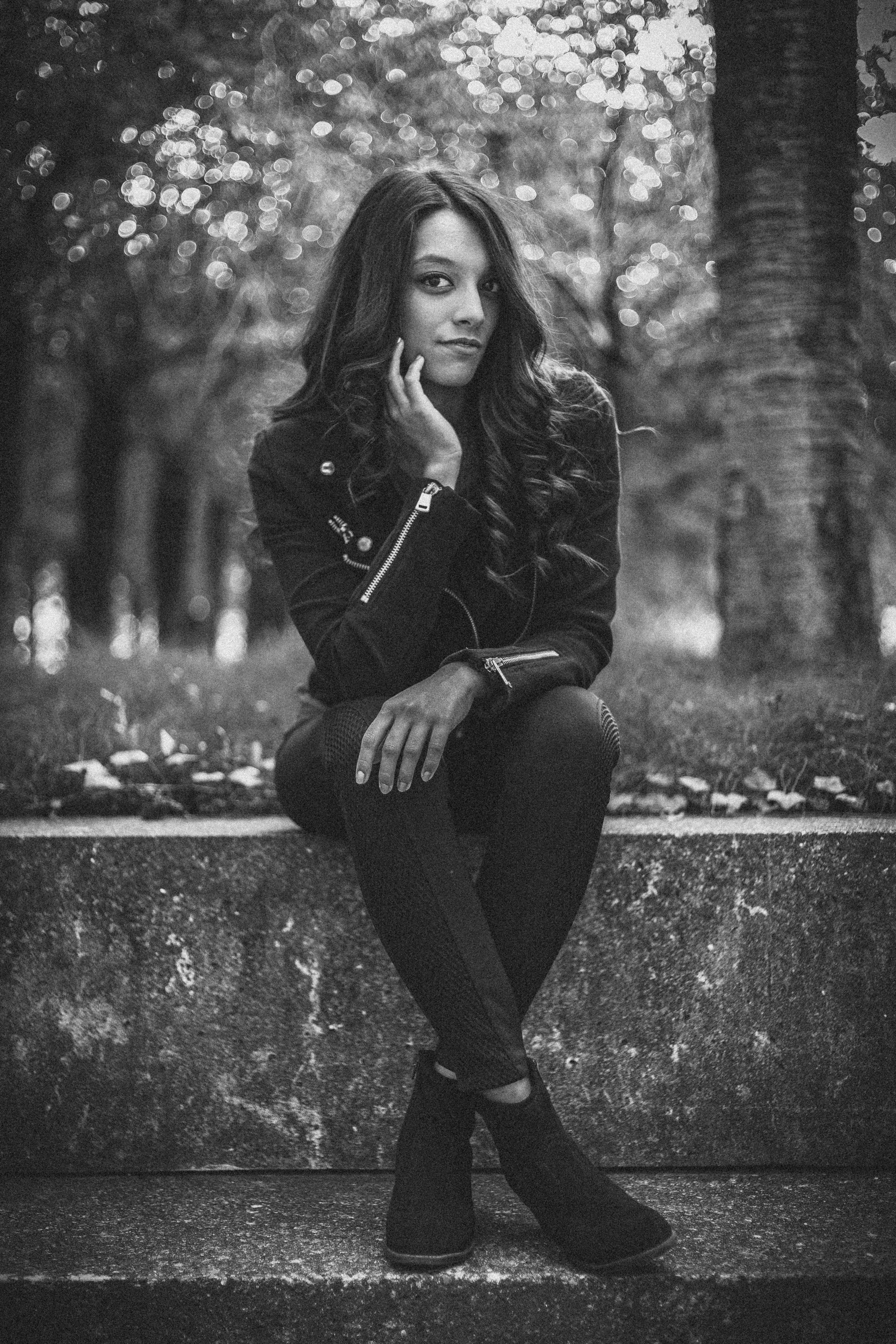 Monochrome Photo of Woman Sitting On Ledge