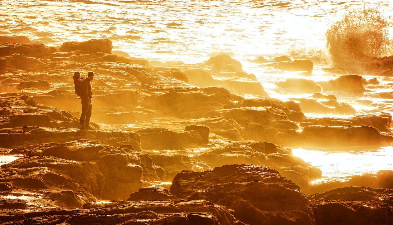 Hombre de pie en la costa rocosa durante el atardecer