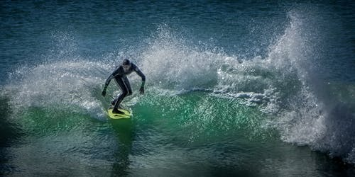 Man Surfing on Body of Water