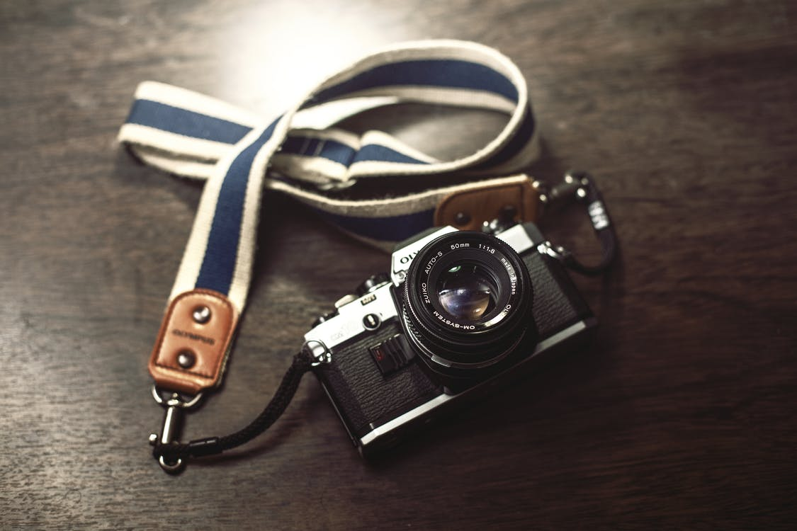 Black and Gray Bridge Camera With White and Blue Lanyard