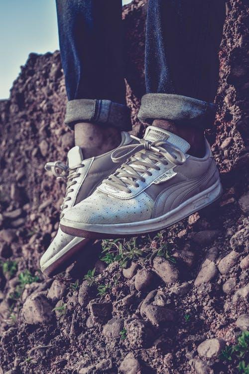 岩石的, 白色的鞋子, 美洲狮, 蓝色牛仔裤 的 免费素材照片