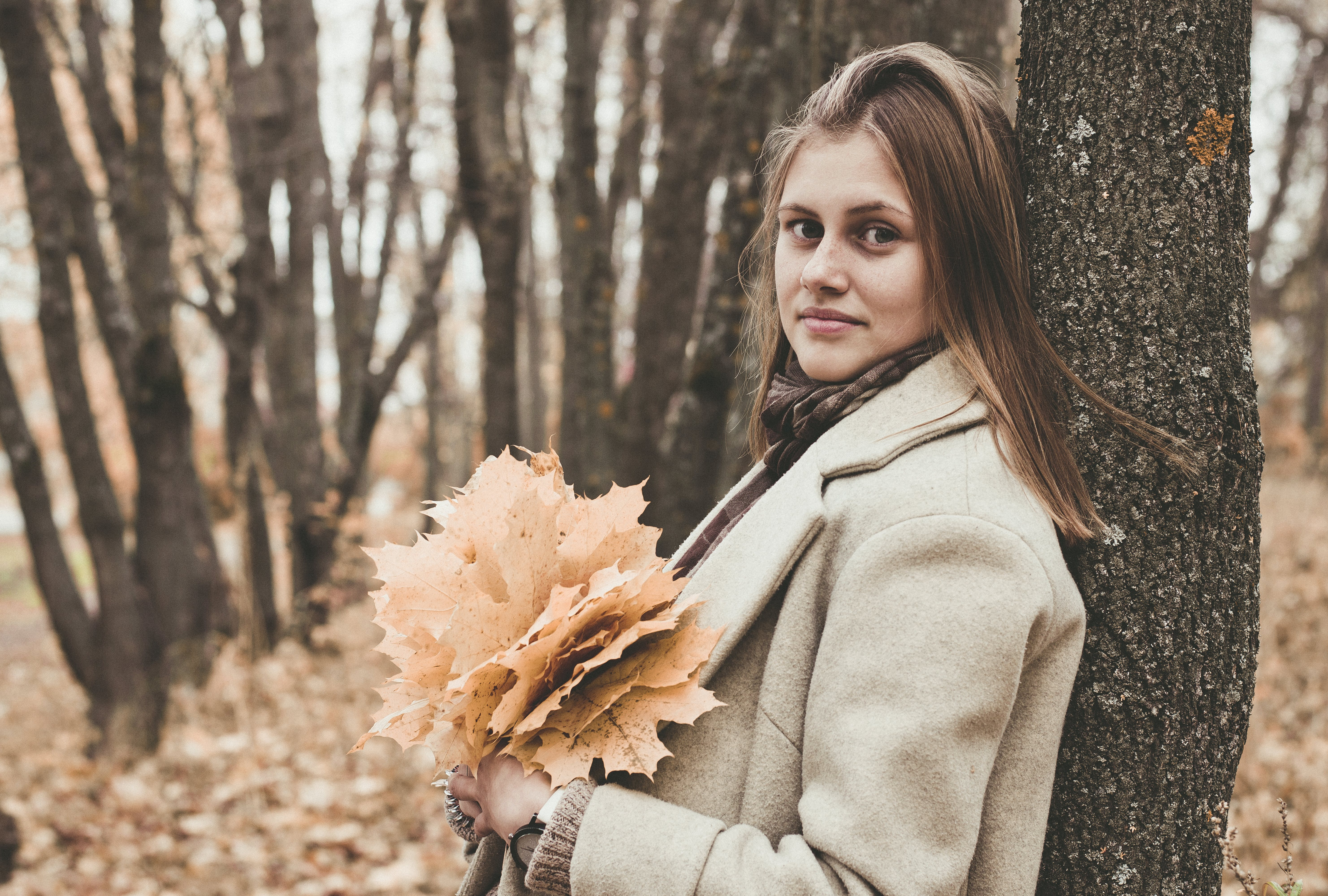 Woman Holding Leaves While Leaning Her Back on Tree
