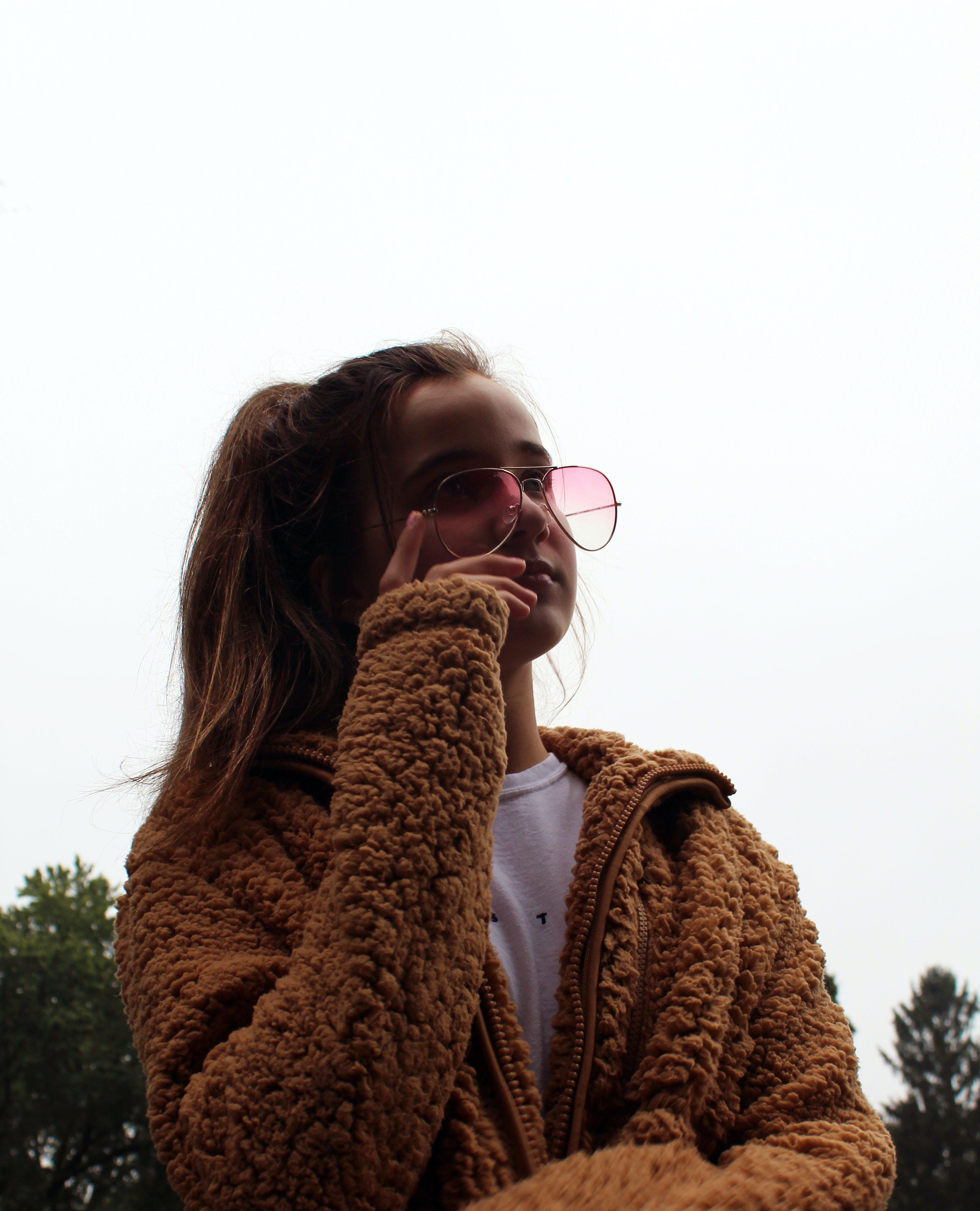 Girl Holding Her Eyeglasses Under White Sky