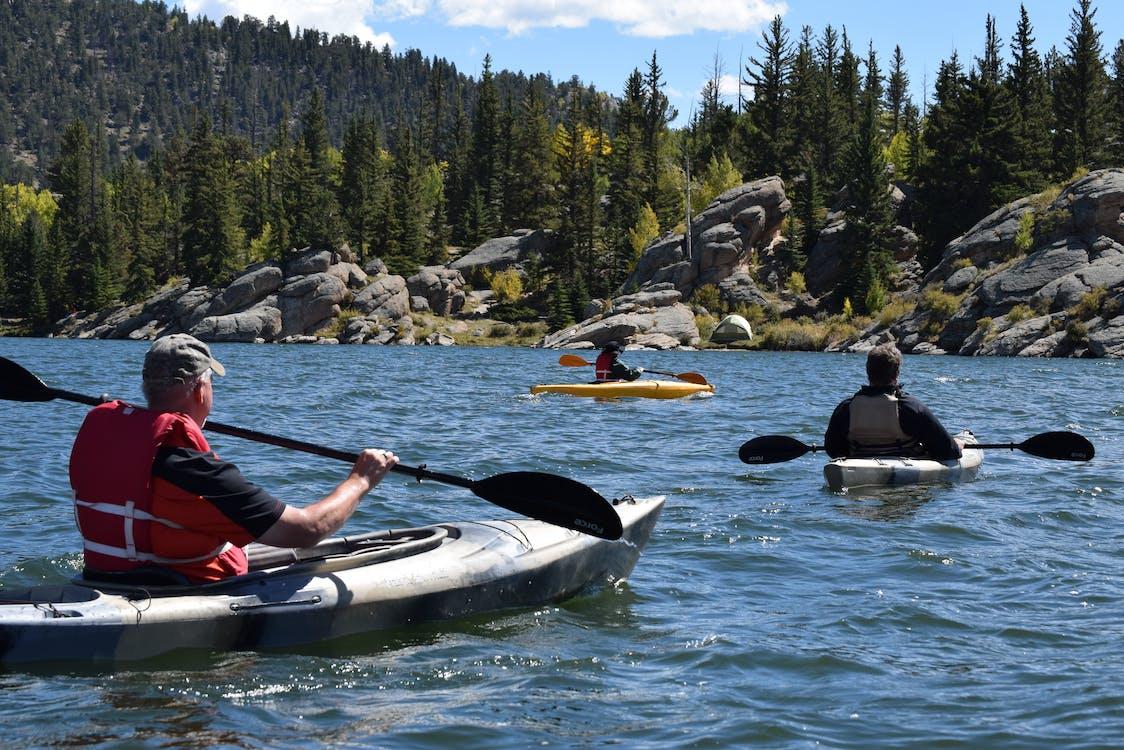 Three Men Riding Kayaks On Body Of Water