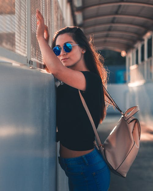 Woman in Black Top Wearing Sunglasses Standing Beside of Wall