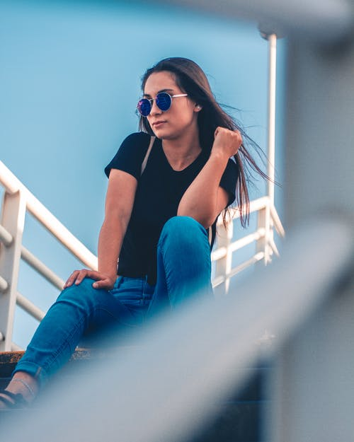 Woman Sitting On Stairs Posing For Photo