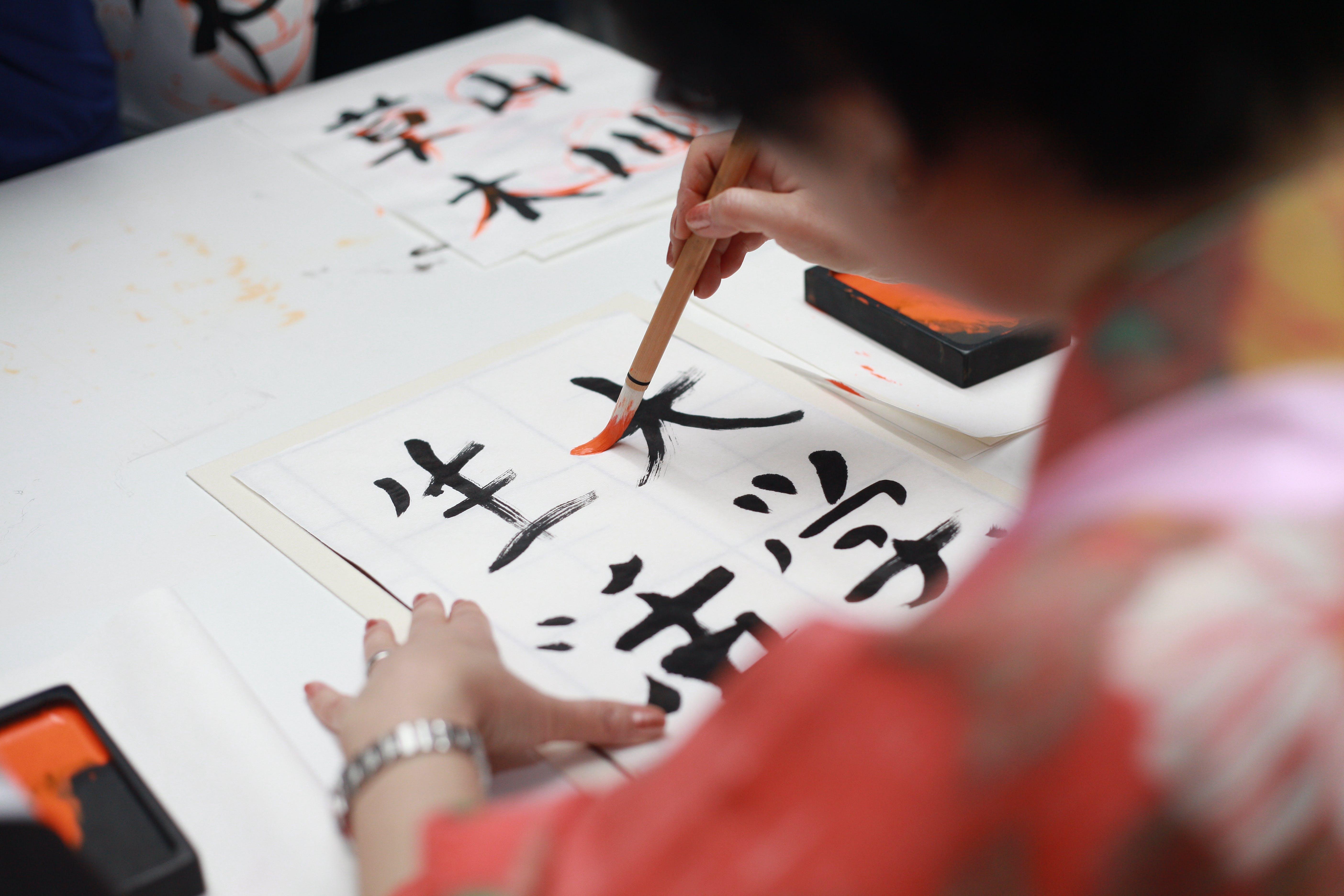 Person Holding Brush Drawing Kanji Script