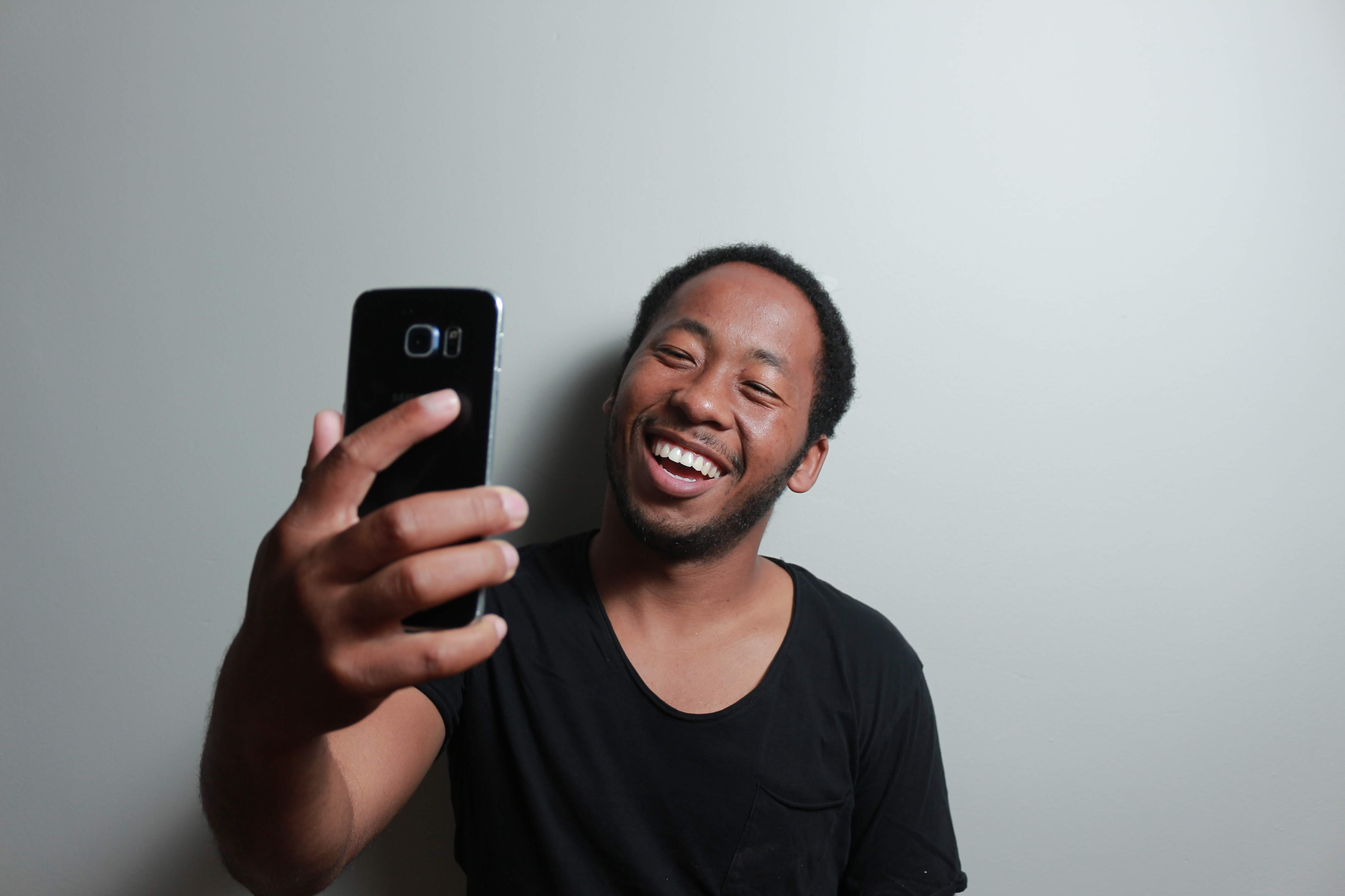 Man Holding Smartphone While Leaning on White Wall