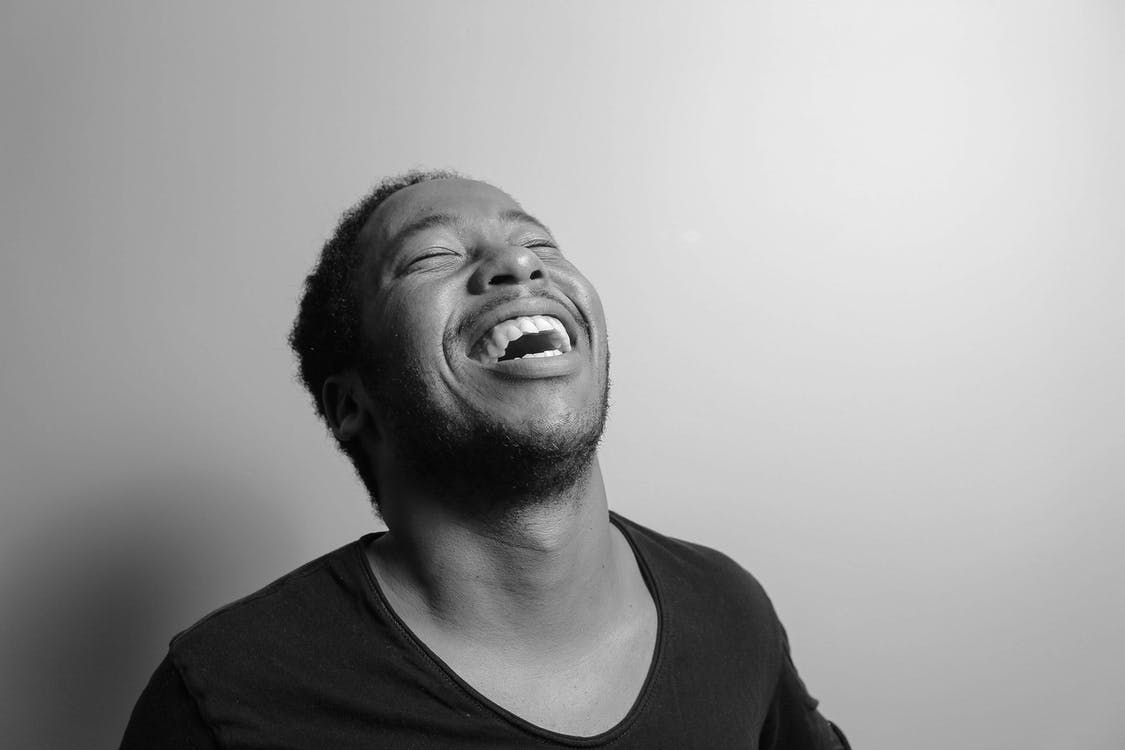 Grayscale Photograph of Man Laughing