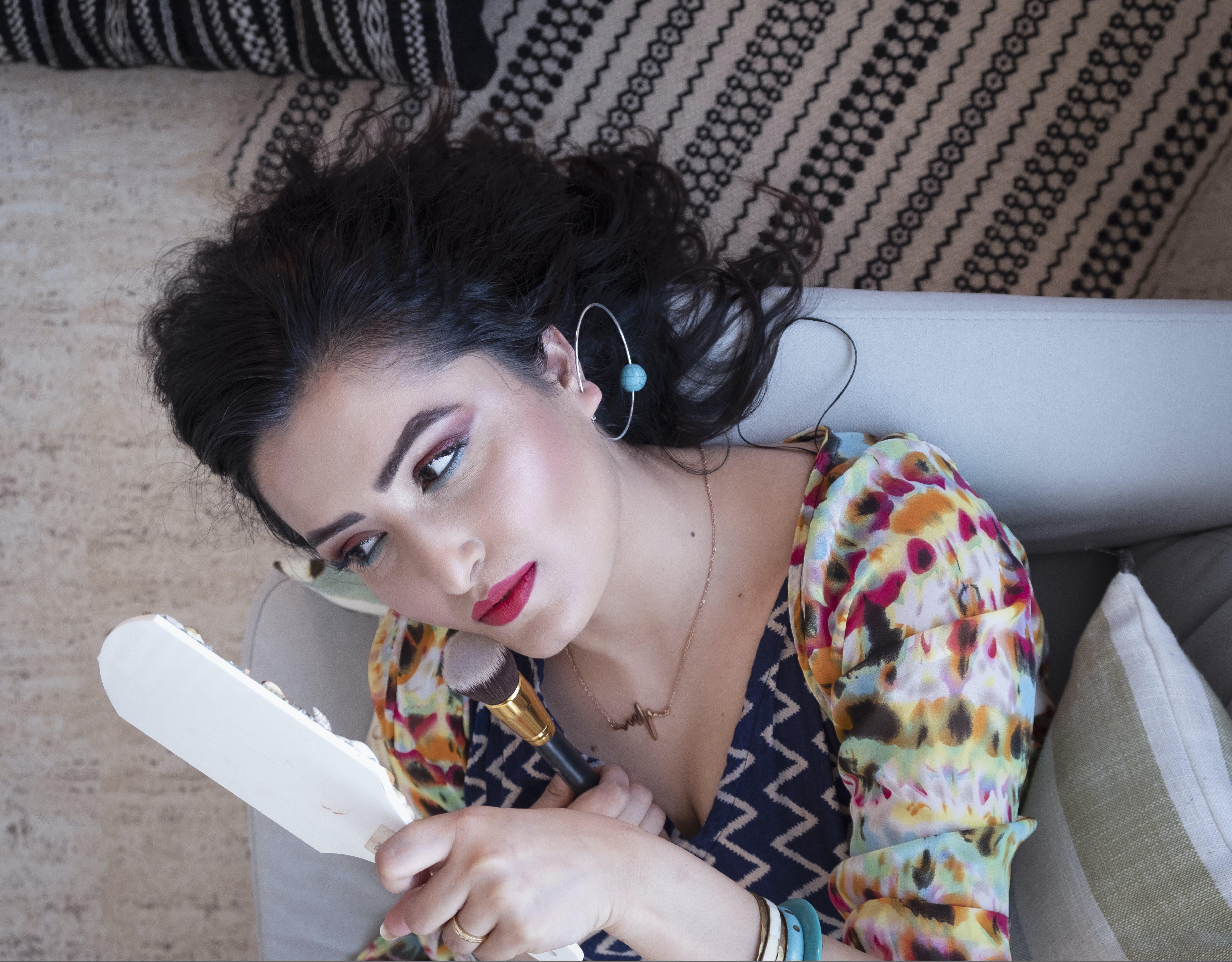 Woman Lying On Sofa Holding Mirror