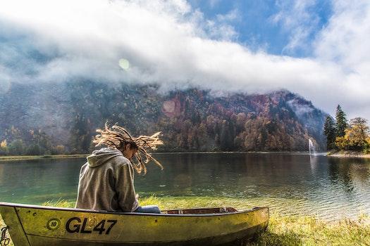 Man in Brown Hoodie Sitting on Yellow Paddle Boat Beside Lake Behind Hills during Daytime