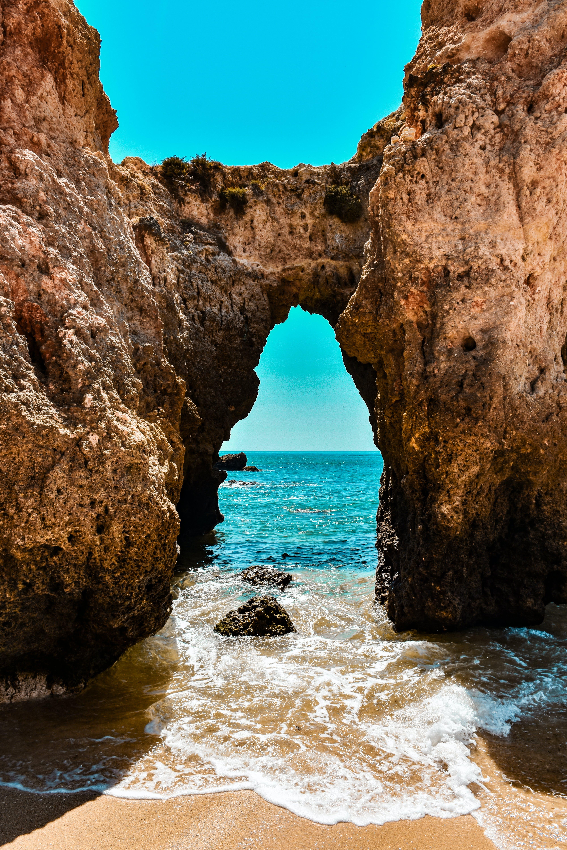 Photo of Rock Formation Near Seashore Under Blue Sky