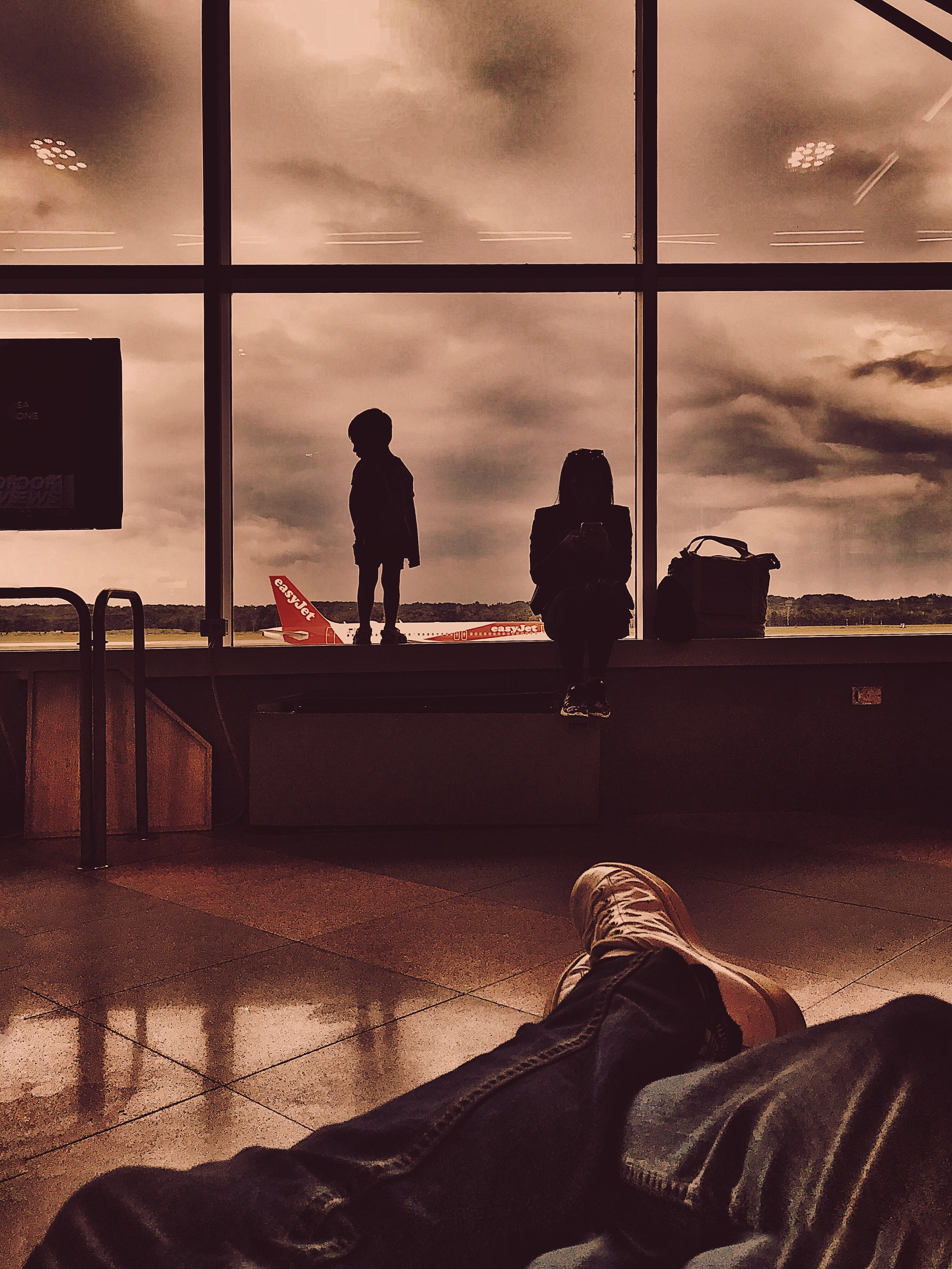 Silhouette of Person and Toddler Sitting on Brown Wooden Table Near Glass Wall
