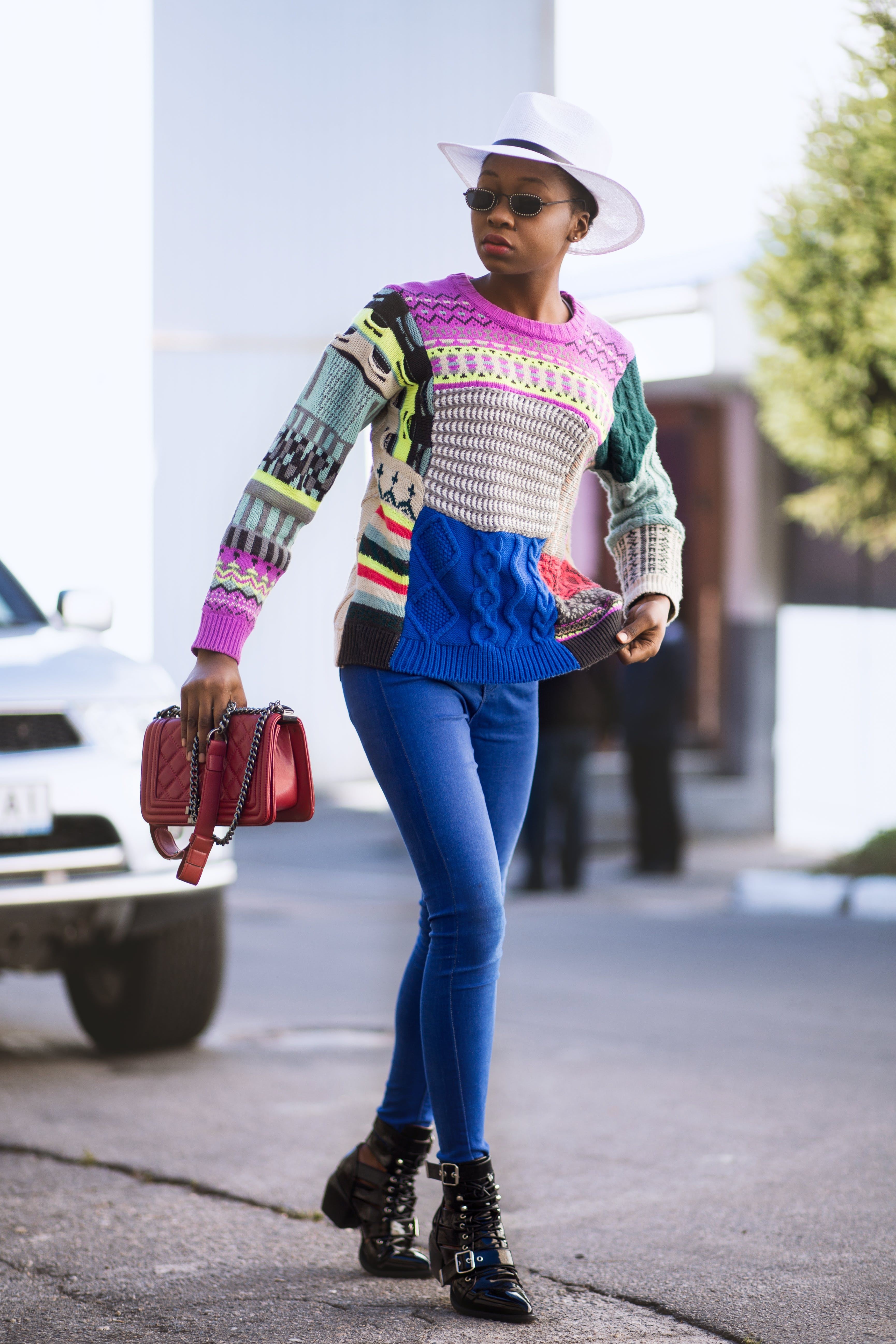 Woman Wearing Multicolored Knit Long-sleeved Top and Blue Denim Skinny Jeans With Hat and Bag on Hand Walking