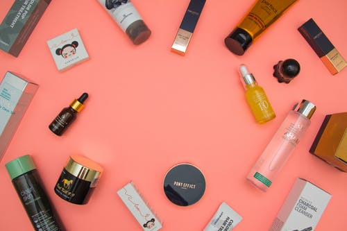 Stylish beauty products arranged on pink table