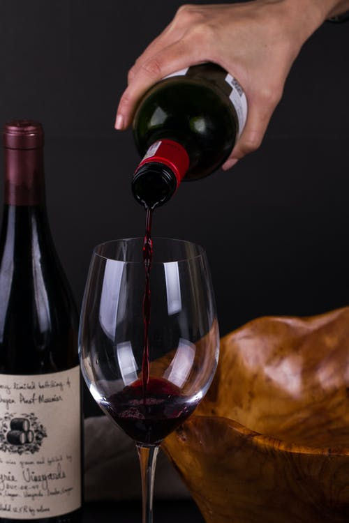 Crop person pouring wine into glass