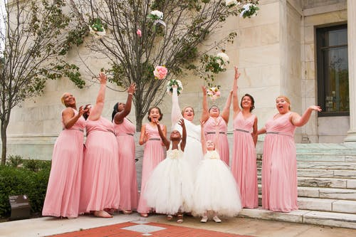 Women Wearing Dresses While Throwing Bouquets