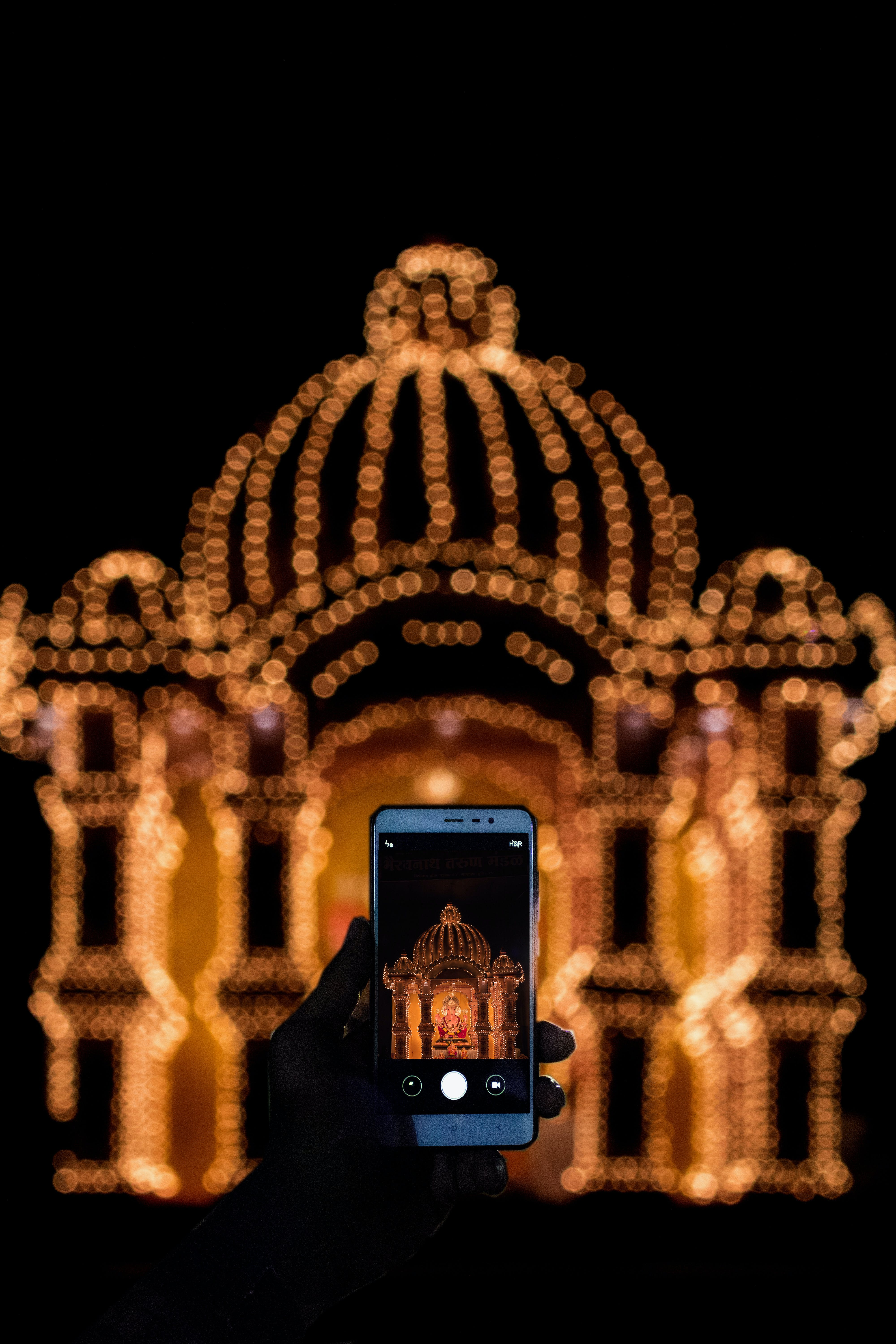 Person Taking Photo of String Light Decor With Smartphone during Nighttime