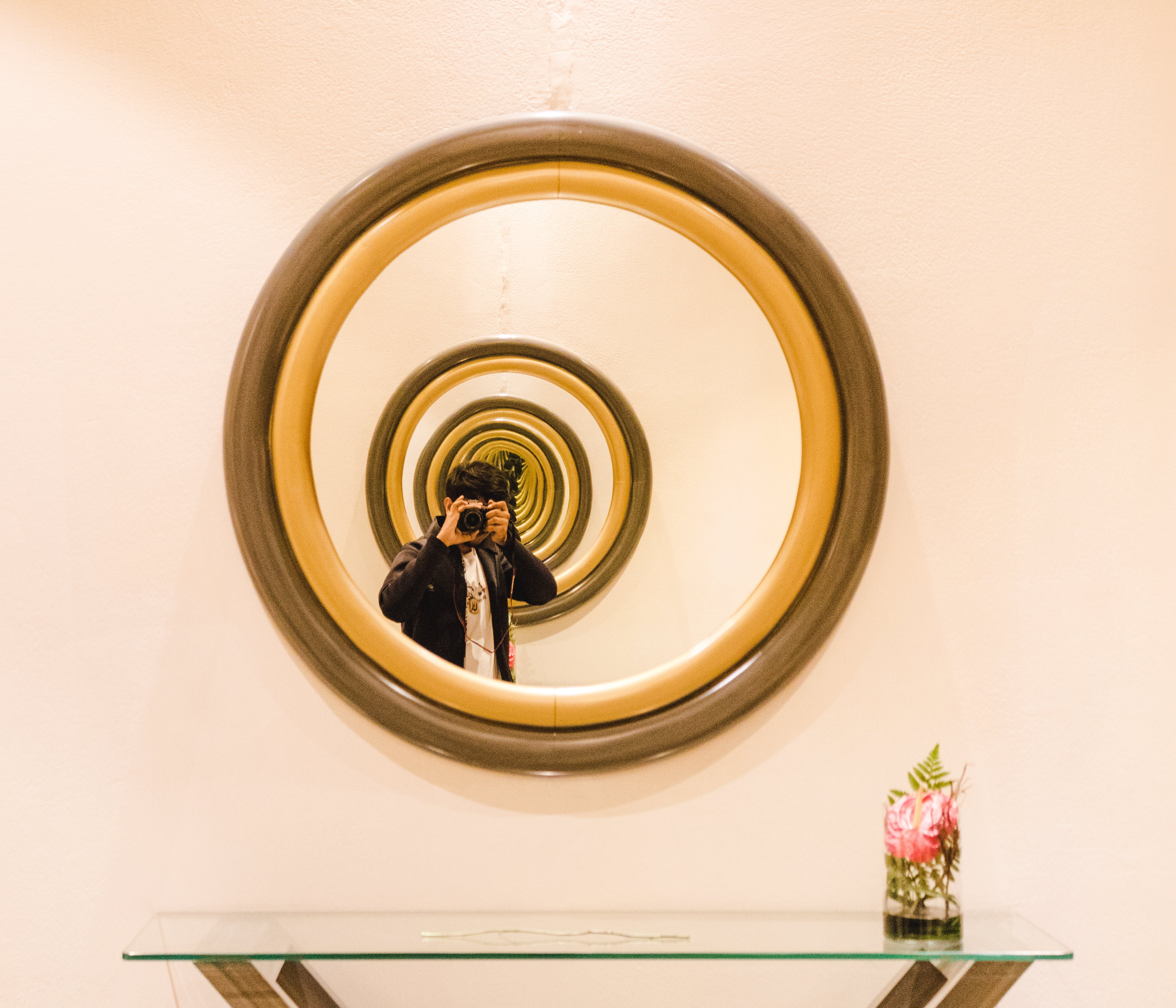 Person Reflect on Round Brown Wooden-framed Mirror