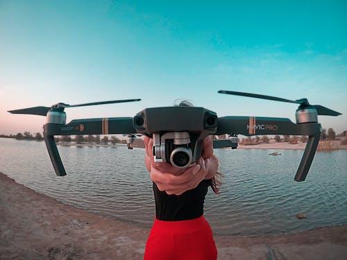 Бесплатное стоковое фото с держать, дрон, женщина, камера